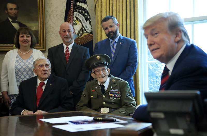 President Donald Trump listens to World War II veterans, seated from left, Paul Kriner and Floyd Wigfield, in the Oval Office of the White House in Washington, Thursday, April 11, 2019. (AP Photo/Manuel Balce Ceneta)