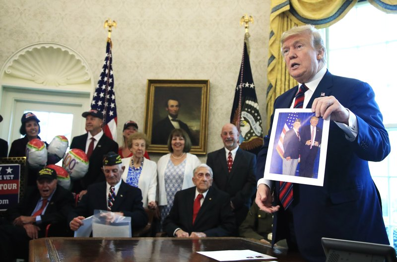 President Donald Trump is presented with a picture by a World War II veteran in the Oval Office of the White House in Washington, Thursday, April 11, 2019. (AP Photo/Manuel Balce Ceneta)