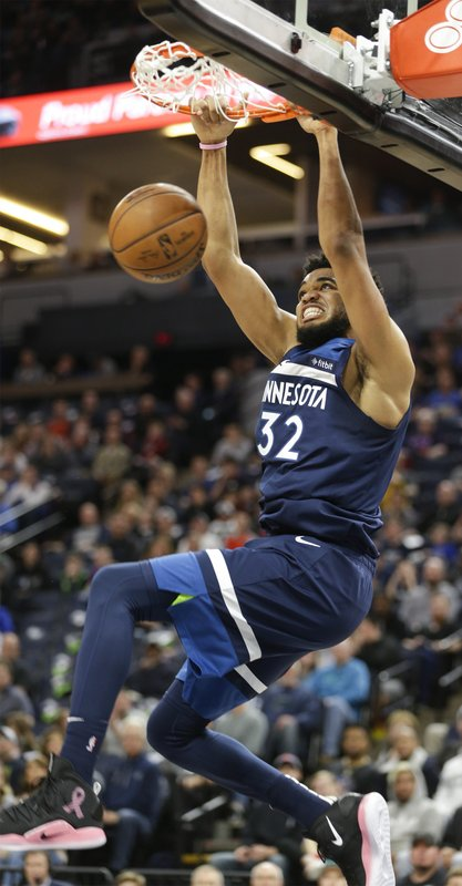 Minnesota Timberwolves center Karl-Anthony Towns (32) dunks during the first half of a NBA basketball game against the Oklahoma City Thunder Sunday, April 7, 2019, in Minneapolis. (AP Photo/Paul Battaglia)