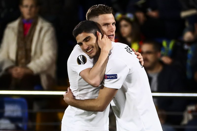 Valencia's Gonzalo Guedes of Valencia, right, celebrates after scoring the opening goal with Kevin Gameiro during the quarterfinal, 1st leg, Europa League soccer match between Villarreal and Valencia at the Ceramica stadium in Villarreal, Spain, Thursday April 11, 2019. (AP Photo/Jose Miguel Fernandez de Velasco)