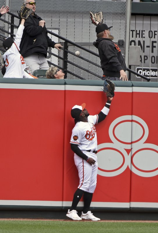 Baltimore Orioles left fielder Dwight Smith Jr., and a fan cannot catch a home run ball hit by Oakland Athletics' Chris Davis for two runs in the fourth inning of a baseball game, Thursday, April 11, 2019, in Baltimore. (Kenneth K. Lam/The Baltimore Sun via AP)