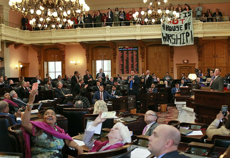 Some members of the Ohio House applaud following their vote while others photograph protestors who unfurled banners reading