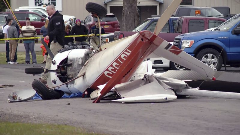 In this image taken from video provided by CNYCENTRAL, SYRACUSE, NY, spectators look at the wreckage of a light airplane after it crash landed on a street in Fulton, N. (CNYCENTRAL, SYRACUSE, NY, via AP)