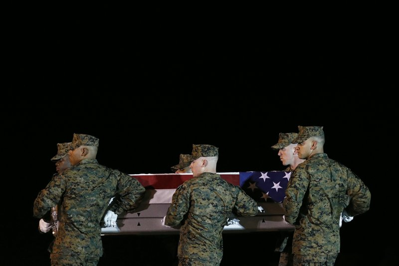 A U.S. Marine Corps carry team moves a transfer case containing the remains of Staff Sgt. Christopher Slutman, Thursday, April 11, 2019, at Dover Air Force Base, Del. (AP Photo/Patrick Semansky)