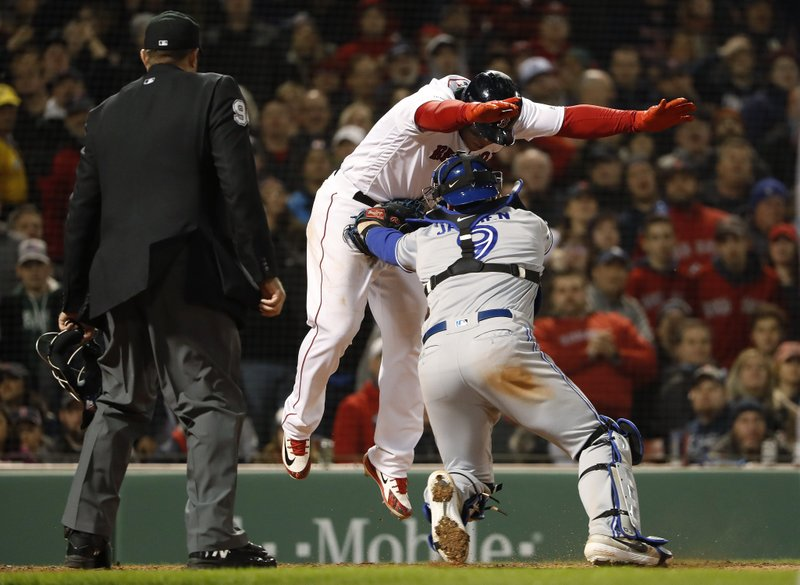 Toronto Blue Jays catcher Danny Jansen tags out Boston Red Sox's Rafael Devers during the fifth inning of a baseball game Thursday, April 11, 2019, at Fenway Park in Boston. (AP Photo/Winslow Townson)