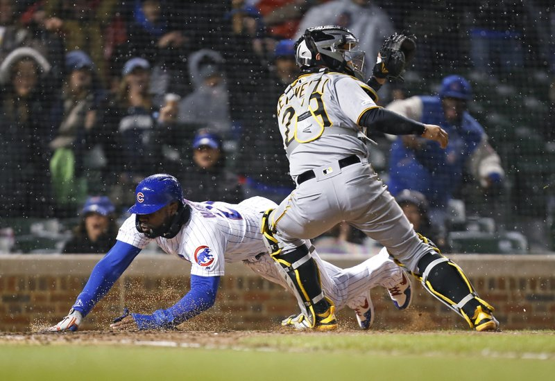 Chicago Cubs' Jason Heyward scores past Pittsburgh Pirates catcher Francisco Cervelli on a single by Daniel Descalso during the seventh inning of a baseball game in Chicago, Thursday, April 11, 2019. (AP Photo/Nuccio DiNuzzo)