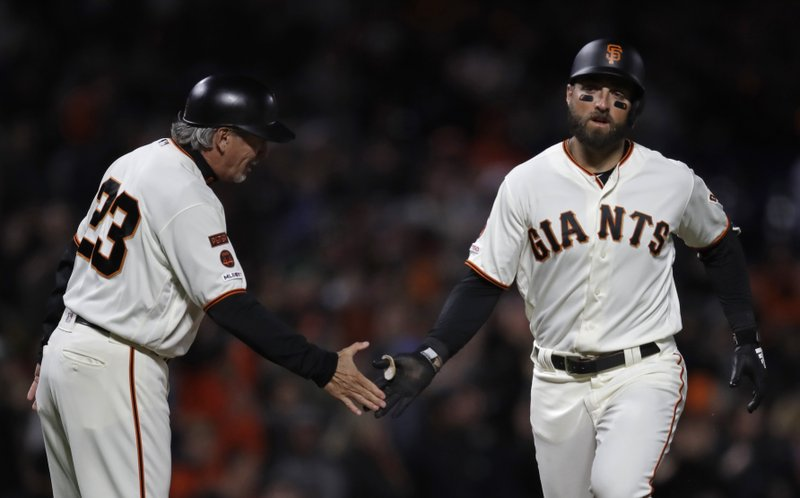San Francisco Giants' Kevin Pillar, right, is congratulated by third base coach Ron Woods after hitting a home run off Colorado Rockies' Jon Gray during the seventh inning of a baseball game Thursday, April 11, 2019, in San Francisco. (AP Photo/Ben Margot)