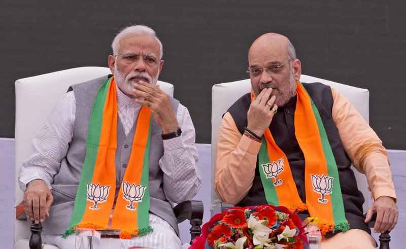 In this April 8, 2019, photo, Indian Prime Minister Narendra Modi, left, with Bharatiya Janata Party (BJP) president Amit Shah listens to Indian Home Minister Rajnath Singh during the release BJP's manifesto for the upcoming general elections in New Delhi. (AP Photo/Manish Swarup)