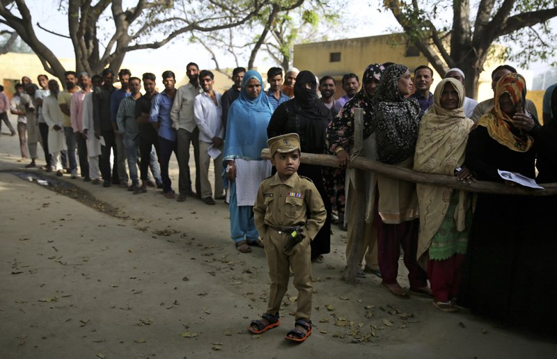 In this April 11, 2019, photo, a young boy dressed as a policeman stands as Indians wait in a queue to cast their votes in village Sawaal near Meerut, Uttar Pradesh, India. (AP Photo/Altaf Qadri)