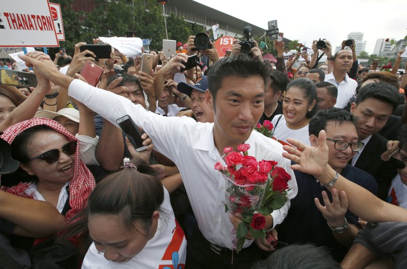 In this April 6, 2019, photo, Thailand's Future Forward Party leader Thanathorn Juangroongruangkit is mobbed by his supporters upon arrival at a police station Bangkok, Thailand. (AP Photo/Sakchai Lalit)