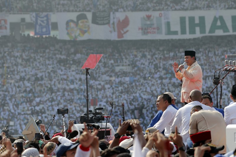 In this April 7, 2019, photo, Indonesian presidential candidate Prabowo Subianto, right, speaks to supporters during a campaign rally of his Great Indonesia Movement Party at Gelora Bung Karno Stadium in Jakarta. (AP Photo/Tatan Syuflana)