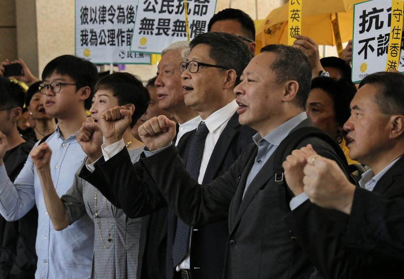 In this April 9, 2019, photo, Occupy Central leaders, from right, Benny Tai, Chan Kin-man, Chu Yiu-ming, Tanya Chan and Eason Chung shout slogans before entering a court in Hong Kong. (AP Photo/Vincent Yu)