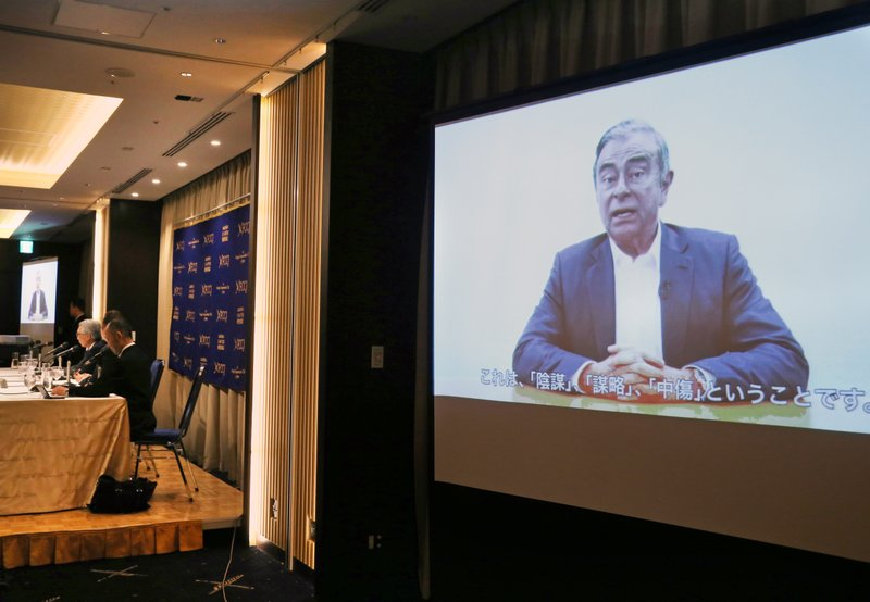 In this April 9, 2019, photo,  former Nissan chairman Carlos Ghosn, seen on a screen, speaks in a video during a press conference held by his lawyers in Tokyo. (AP Photo/Koji Sasahara)