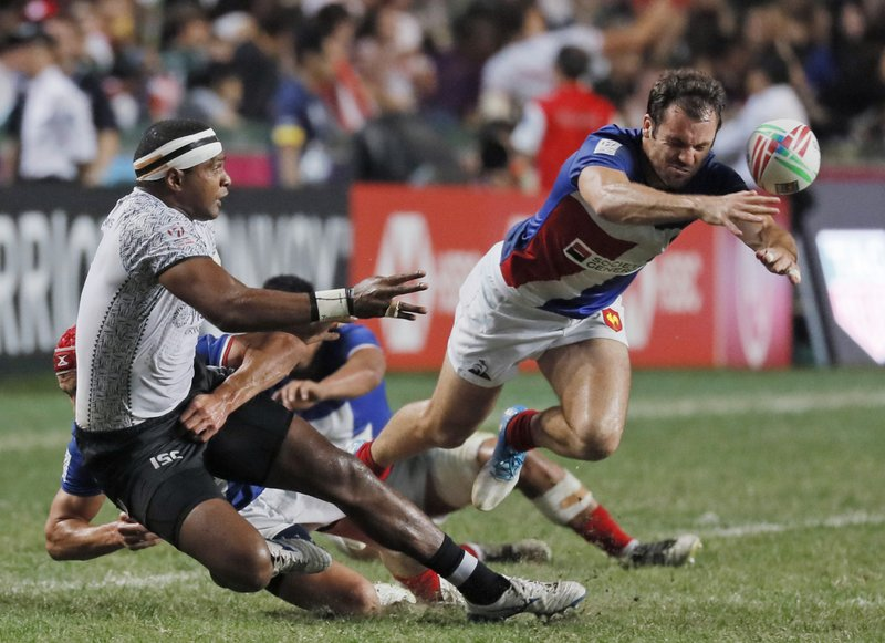 In this April 7, 2019, photo, Fiji's Aminiasi Tuimaba, left, passes the ball to teammate as France's Paul Bonnefond, right tries to block during the final match at the Hong Kong Sevens rugby tournament in Hong Kong. (AP Photo/Kin Cheung)