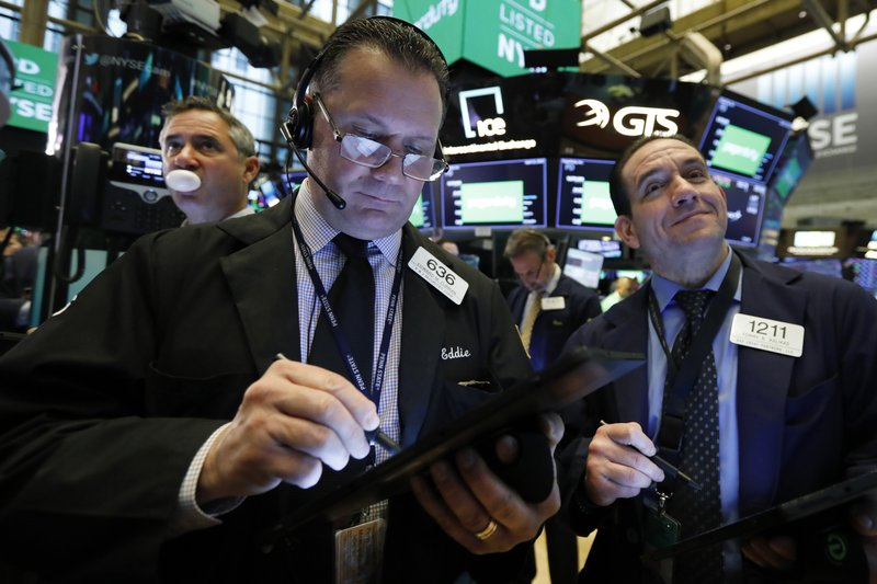 Traders Edward Curran, center, and Tommy Kalikas, right, work on the floor of the New York Stock Exchange, Thursday, April 11, 2019. (AP Photo/Richard Drew)