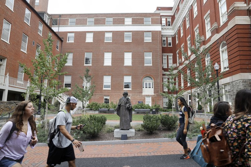FILE - In this Sept. 1, 2016 file photo, students walk past a Jesuit statue in front of Isaac Hawkins Hall, center, formerly named Mulledy Hall, on the Georgetown University campus, in Washington. (AP Photo/Jacquelyn Martin, File)