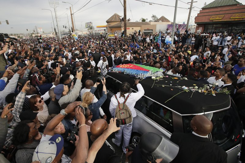 A hearse carrying the casket of slain rapper Nipsey Hussle, draped in the flag of his father's native country, Eritrea in East Africa, passes through the crowd Thursday, April 11, 2019, in Los Angeles. (AP Photo/Jae C. Hong)