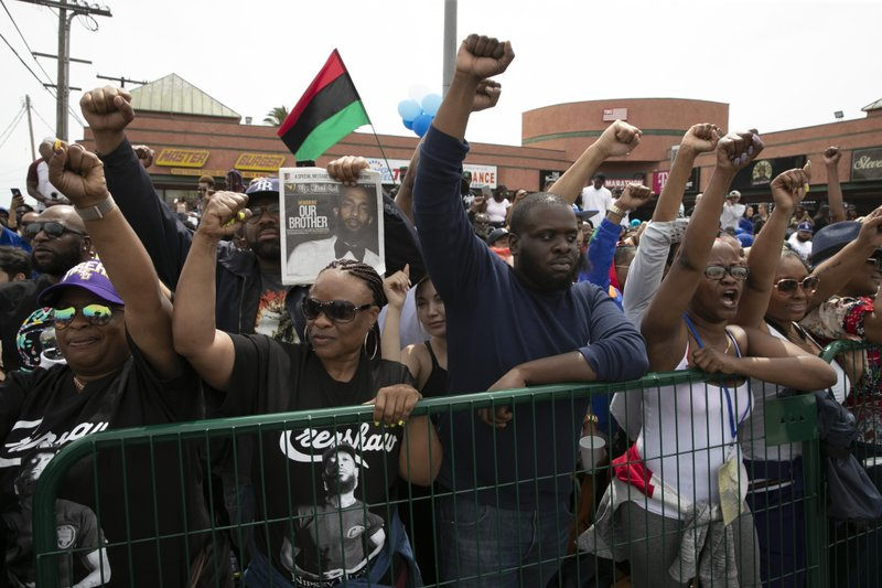 People hold up their fists while waiting for a hearse carrying the casket of slain rapper Nipsey Hussle to pass by in front of Hussle's clothing store The Marathon Thursday, April 11, 2019, in Los Angeles. (AP Photo/Jae C. Hong)