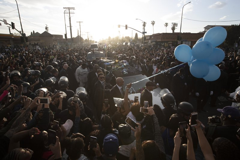 A hearse carrying the casket of slain rapper Nipsey Hussle passes through a large crowd on its 25-mile trek through the streets of the city Thursday, April 11, 2019, in Los Angeles. (AP Photo/Jae C. Hong)