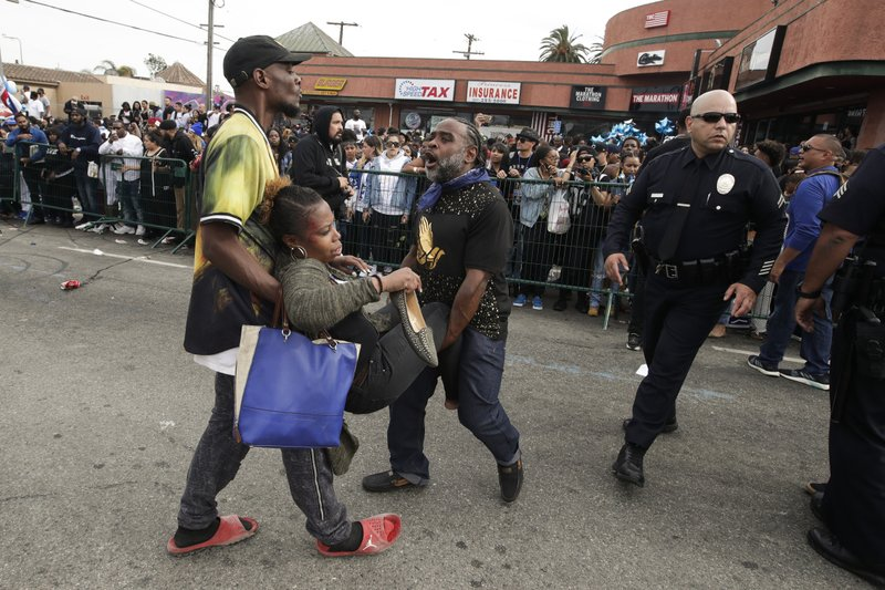 Two men carry a woman injured in a stampede as people gather to watch a hearse carrying the casket of slain rapper Nipsey Hussle Thursday, April 11, 2019, in Los Angeles. (AP Photo/Jae C. Hong)