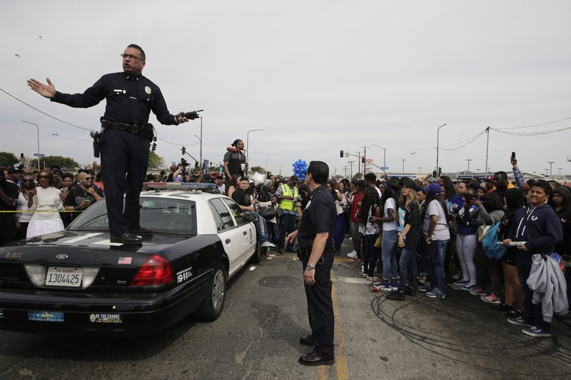 Los Angeles police officers tell the crowd to back up to clear the way for a hearse carrying the casket of slain rapper Nipsey Hussle Thursday, April 11, 2019, in Los Angeles. (AP Photo/Jae C. Hong)