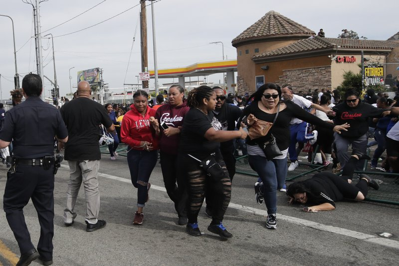 People flee the scene after hearing a loud noise while waiting for a hearse carrying the casket of slain rapper Nipsey Hussle Thursday, April 11, 2019, in Los Angeles. (AP Photo/Jae C. Hong)