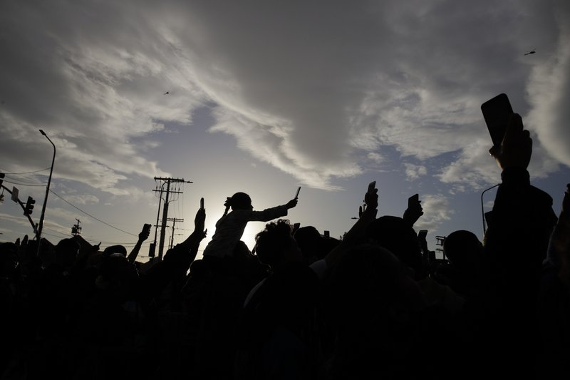 People hold up their smartphones to record as a hearse carrying the casket of slain rapper Nipsey Hussle passes by Thursday, April 11, 2019, in Los Angeles. (AP Photo/Jae C. Hong)