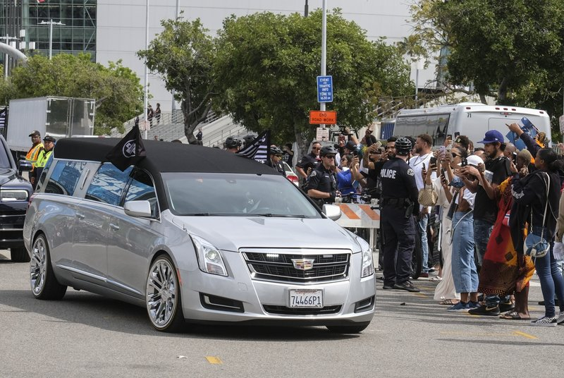 The hearse carrying rapper Nipsey Hussle leaves the Staples Center after a memorial service in Los Angeles, Thursday, April 11, 2019. (AP Photo/Ringo H.W. Chiu)