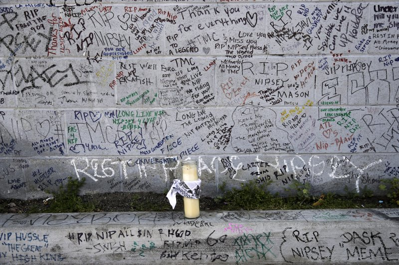 A lone candle rests against a wall full of messages commemorating slain rapper Nipsey Hussle outside The Marathon Clothing store as people wait for a funeral procession to pass Thursday, April 11, 2019, in Los Angeles. (AP Photo/Jae C. Hong)
