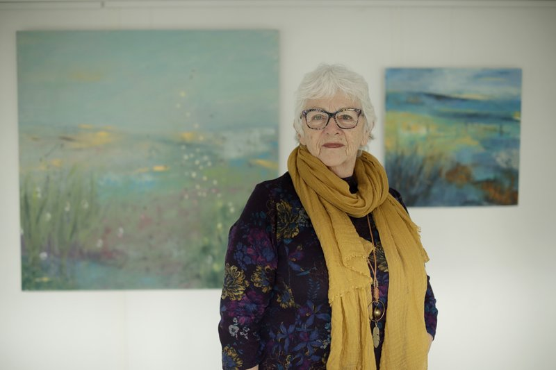 Elly Wright, a Dutch painter who has lived in Britain for 51-years, poses for photographs backdropped by two of her paintings at her home in Epsom, on the south west edge of London, Wednesday, April 10, 2019. (AP Photo/Matt Dunham)