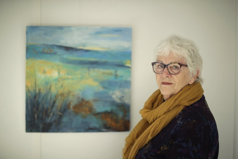 Elly Wright, a Dutch painter who has lived in Britain for 51-years, poses for photographs next to one of her own paintings at her home in Epsom, on the south west edge of London, Wednesday, April 10, 2019. (AP Photo/Matt Dunham)