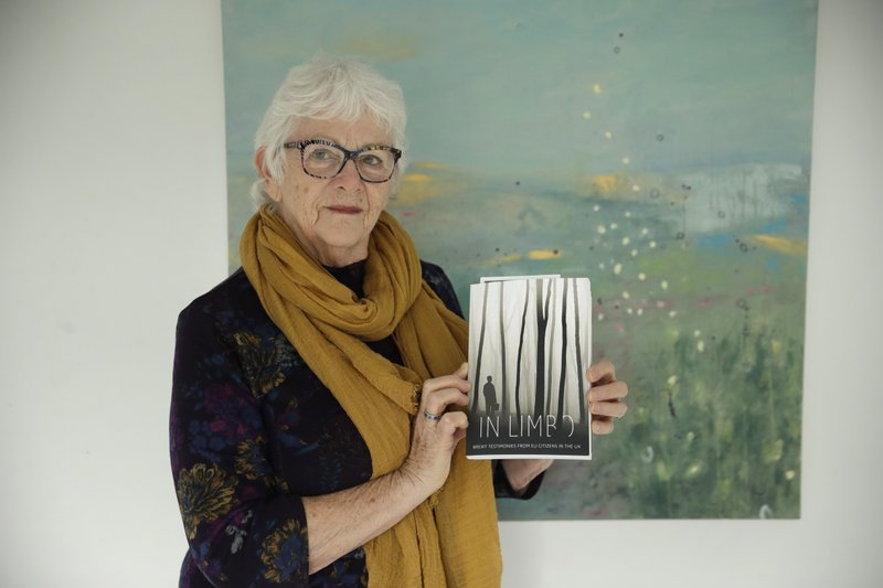 Elly Wright, a Dutch painter who has lived in Britain for 51-years, poses for photographs with a copy of the book