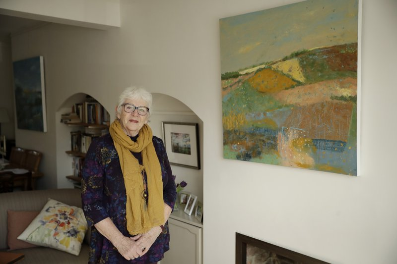 Elly Wright, a Dutch painter who has lived in Britain for 51-years, poses for photographs next to one of her paintings at her home in Epsom, on the south west edge of London, Wednesday, April 10, 2019. (AP Photo/Matt Dunham)