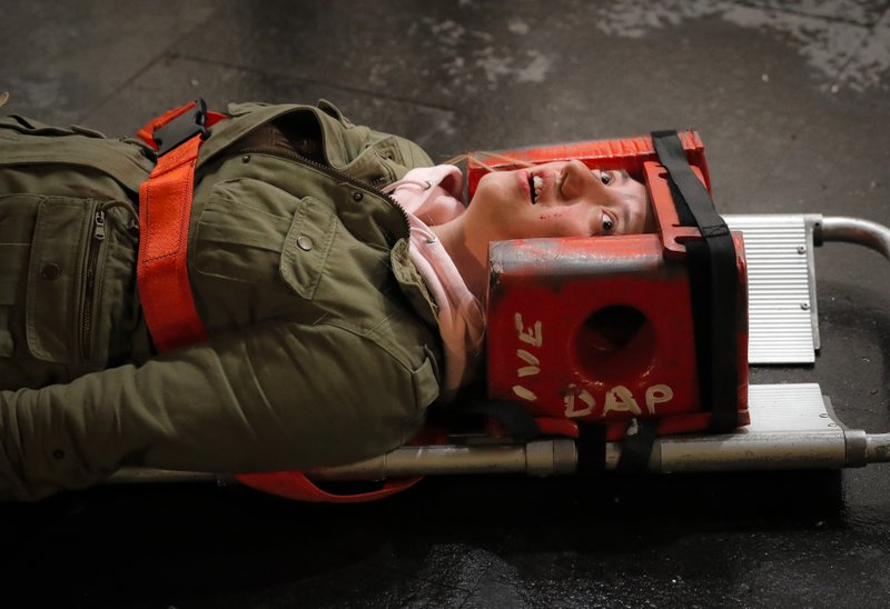 A volunteer posing as a victim screams during a rescue exercise in Bucharest, Romania, Friday, April 12, 2019. (AP Photo/Vadim Ghirda)