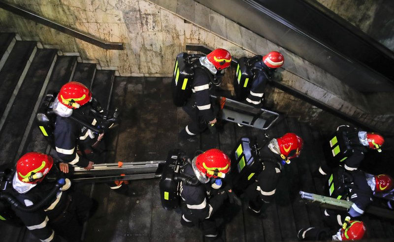 Emergency workers enter a subway station during a rescue exercise in Bucharest, Romania, early Friday, April 12, 2019. (AP Photo/Vadim Ghirda)