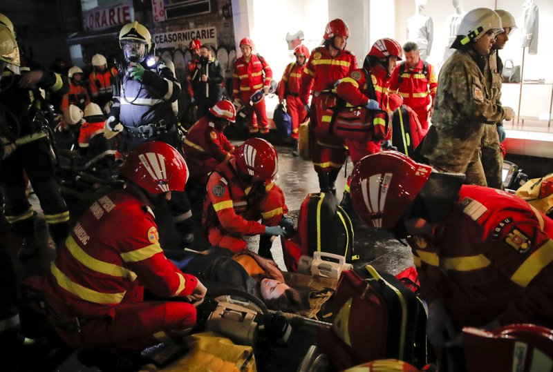 Emergency workers attend to volunteers posing as victims during a rescue exercise in Bucharest, Romania, early Friday, April 12, 2019. (AP Photo/Vadim Ghirda)