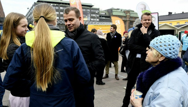 The chairman of The National Coalition Party, parliament member candidate Petteri Orpo speaking with peope while campaigning in Helsinki, Finland, on Thursday, April 11, 2019. (Martti Kainulainen/Lehtikuva via AP)