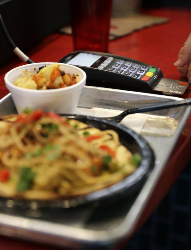 FILE - In this April 10, 2018, file photo, a customers uses a credit card machine to pay for food at Peli Peli Kitchen in Houston. (AP Photo/David J. Phillip, File)