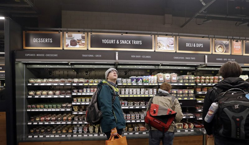 FILE - In this Jan. 22, 2018, file photo, a customer looks overhead in an Amazon Go store, where sensors and cameras are part of a system used to tell what people have purchased and charge their Amazon account in Seattle. (AP Photo/Elaine Thompson, File)