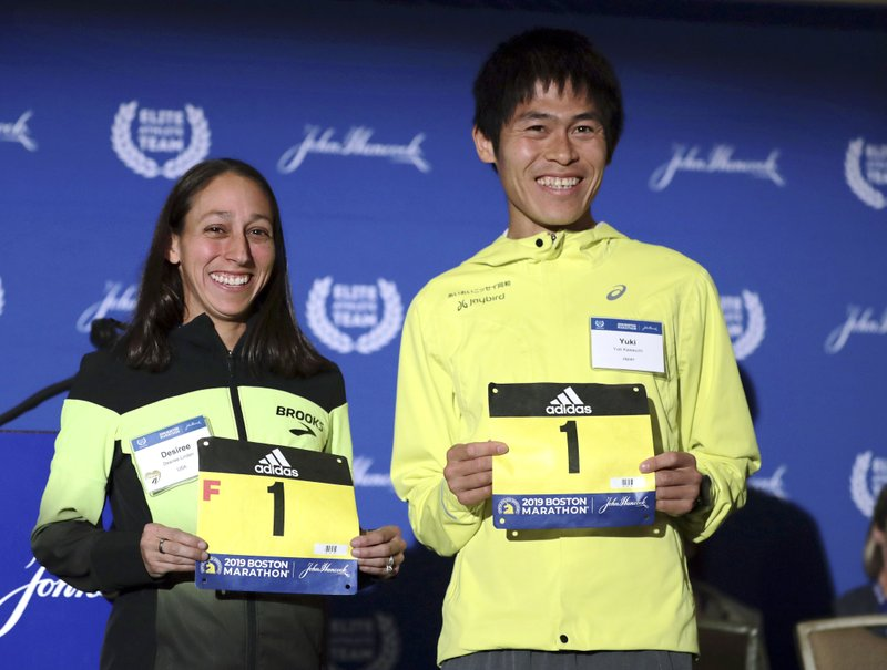 Desiree Linden, left, of Washington, Mich., and Yuki Kawauchi, of Japan, display their assigned bib numbers during a media availability on Friday, April 12, 2019, in Boston in advance of the 123rd Boston Marathon on Monday. (AP Photo/Charles Krupa)