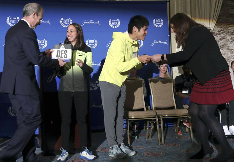 Desiree Linden, left, of Washington, Mich., and Yuki Kawauchi, of Japan, receive their assigned bib numbers during a media availability on Friday, April 12, 2019, in Boston in advance of the 123rd Boston Marathon on Monday. (AP Photo/Charles Krupa)