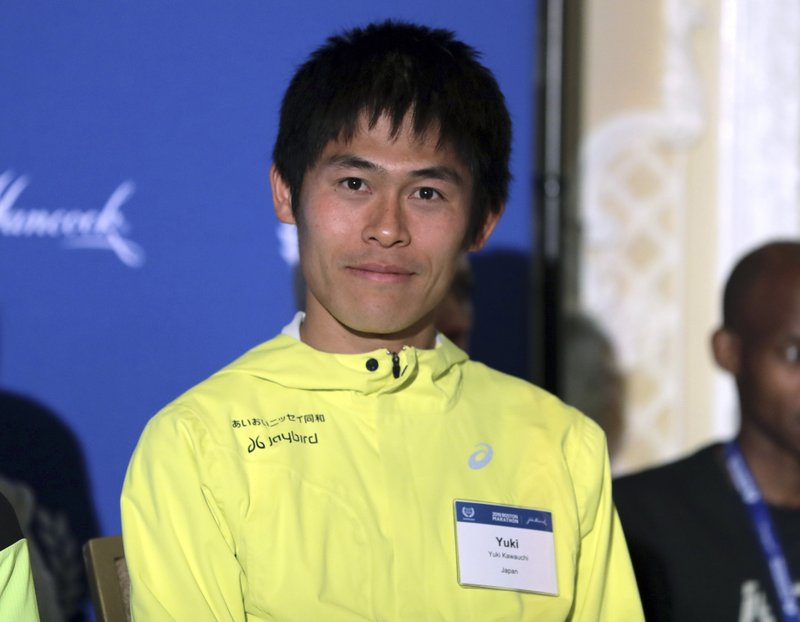 Yuki Kawauchi, center, of Japan, sits on the stage during a media availability on Friday, April 12, 2019, in Boston in advance of the 123rd Boston Marathon on Monday. (AP Photo/Charles Krupa)