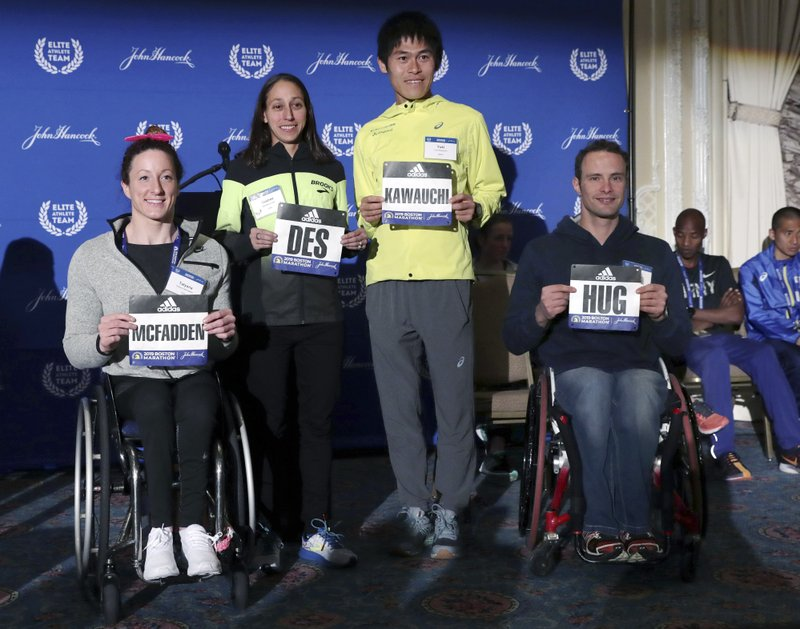 From left Tatyana McFadden, of Clarksville, Md., Desiree Linden, of Washington, Mich., Yuki Kawauchi, center, of Japan, and Marcel Hug, of Switzerland, hold their name signs during a media availability on Friday, April 12, 2019, in Boston in advance of the 123rd Boston Marathon on Monday. (AP Photo/Charles Krupa)