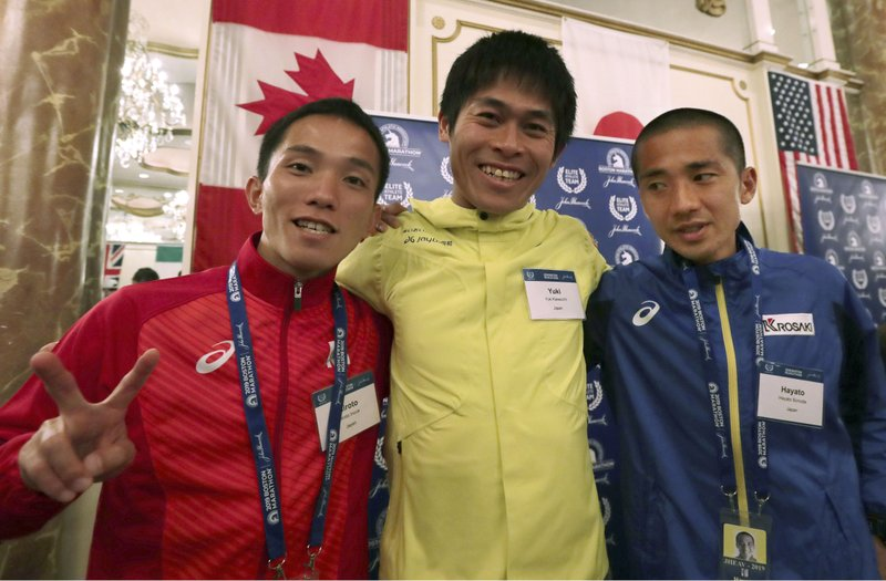 Elite runners Hiroto Inoue, left, Yuki Kawauchi, center, and Hayato Sonoda, all of Japan, pose for a photo after a media availability on Friday, April 12, 2019, in Boston in advance of the 123rd Boston Marathon on Monday. (AP Photo/Charles Krupa)
