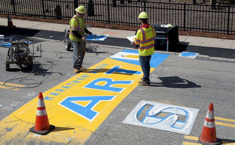 Will Belazoos, left, and Connor Freitas, of Road Safe Traffic Systems, paint the starting line Thursday, April 11, 2019, in Hopkinton, Mass. (Art Illman/The Metro West Daily News via AP)