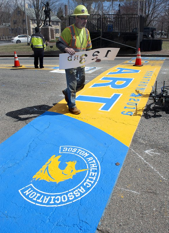 Belazoos of Road Safe Traffic Systems carries a stencil as they paint the starting line Thursday, April 11, 2019, in Hopkinton, Mass. (Art Illman/The Metro West Daily News via AP)