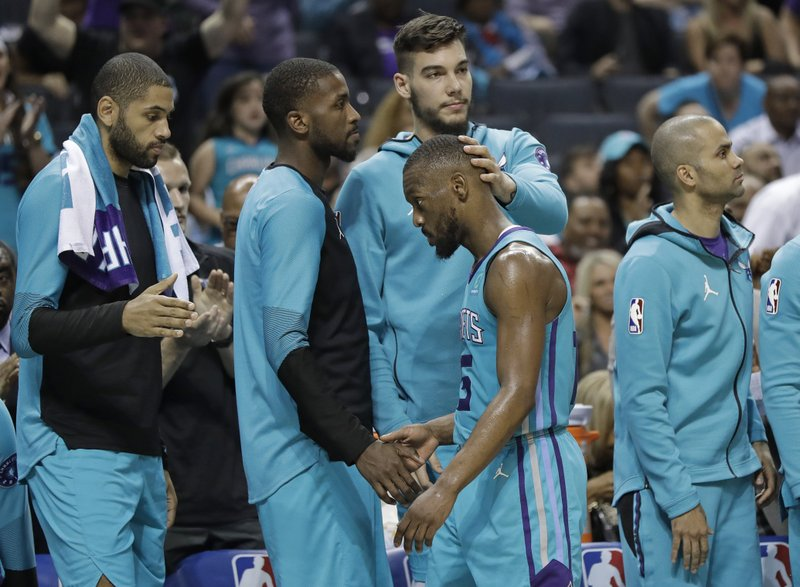 Charlotte Hornets' Kemba Walker, center, is greeted by teammates as he leaves the NBA basketball game against the Orlando Magic late in the second half, in Charlotte, N. (AP Photo/Chuck Burton)