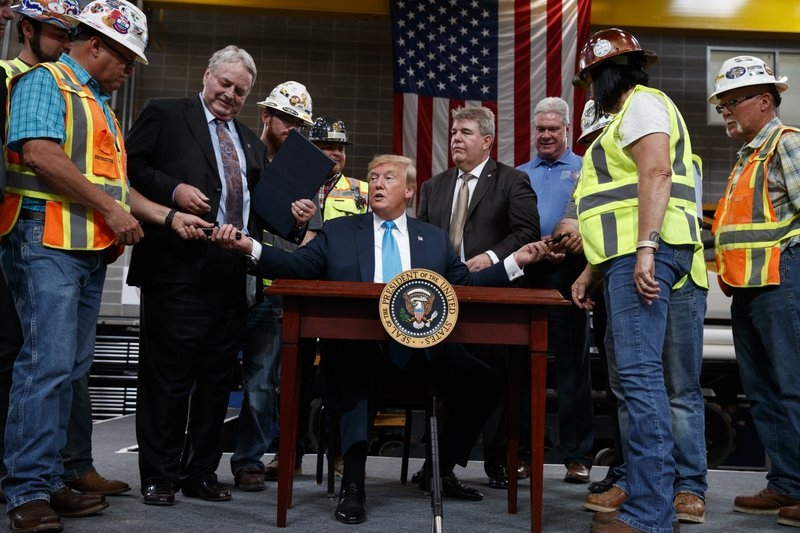 President Donald Trump hands out pens after signing an executive order on energy and infrastructure at the International Union of Operating Engineers International Training and Education Center, Wednesday, April 10, 2019, in Crosby, Texas. (AP Photo/Evan Vucci)