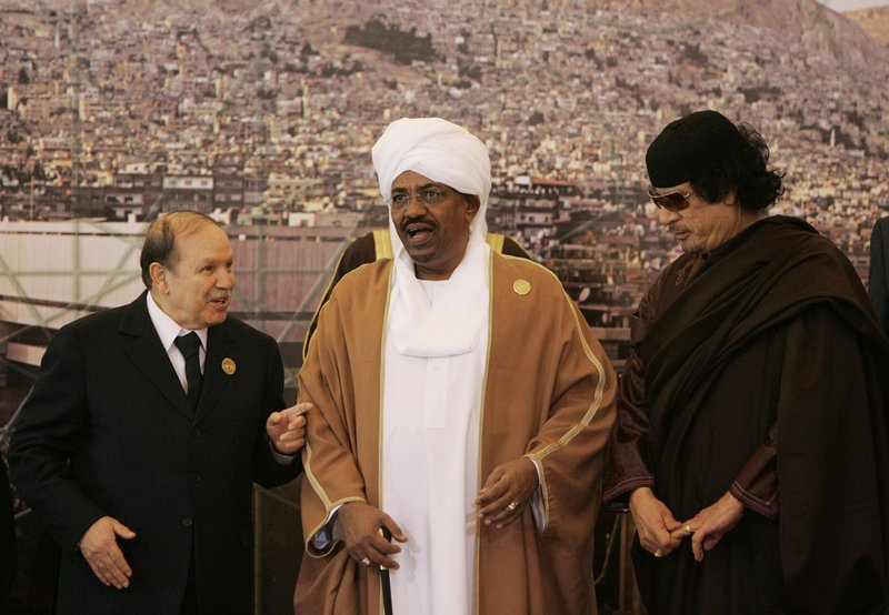 FILE - In this March 29, 2008, file photo, Algerian President Abdelaziz Bouteflika, left, speaks with Sudanese President Omar Al-Bashir, center, and Libyan leader Moammar Gadhafi, right, during the opening session of the Arab Summit in Damascus, Syria. (AP Photo/Hussein Malla, File)