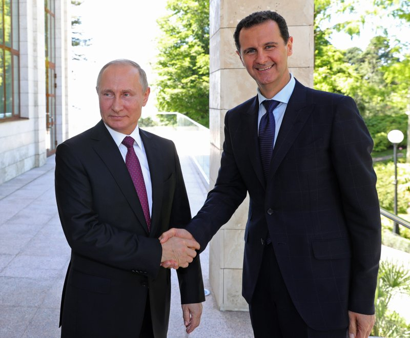 FILE - In this May 17, 2018, file photo, Russian President Vladimir Putin, left, shakes hands with Syrian President Bashar al-Assad during their meeting in the Black Sea resort of Sochi, Russia. (Mikhail Klimentyev, Sputnik, Kremlin Pool Photo via AP, File)